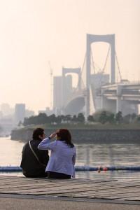 Una pareja en una cita en Odaiba, con el Rainbow Bridge al fondo.