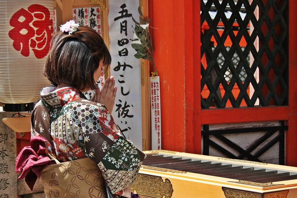 Imagen de una fiel en oración frente al santuario de Jishu Jinja en Kioto